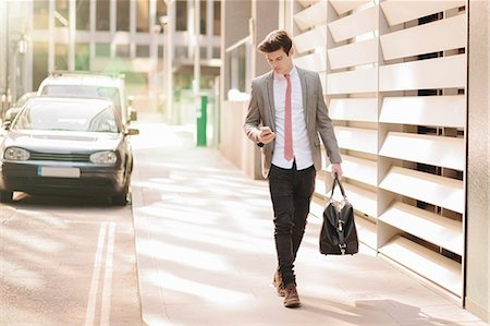 Young city businessman reading smartphone texts whilst walking outside office Stock Photo - Premium Royalty-Free, Code: 649-08125478