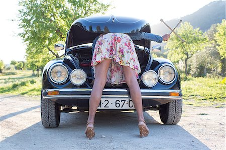 Mature woman bent over car, looking in bonnet Stock Photo - Premium Royalty-Free, Code: 649-08125546
