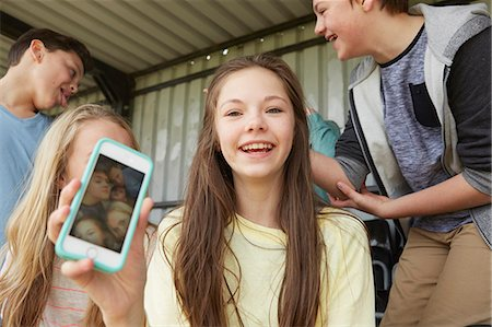 Girl holding up smartphone selfie of friends in shelter Stock Photo - Premium Royalty-Free, Code: 649-08125591