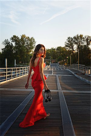 Portrait of a young woman in a smart red dress walking away and looking over shoulder Stock Photo - Premium Royalty-Free, Code: 649-08125653