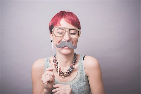 Studio portrait of young woman holding up mustache and spectacles in front of face Stock Photo - Premium Royalty-Free, Code: 649-08125673