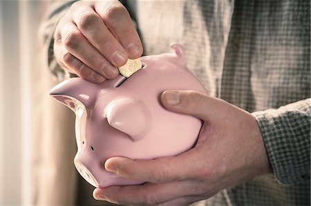 Man inserting coin into piggy bank Stock Photo - Premium Royalty-Free, Code: 649-08125861