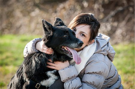 Portrait of mid adult woman kissing her dog in field Stock Photo - Premium Royalty-Free, Code: 649-08125934