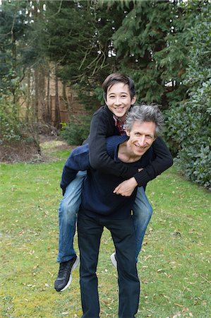 sweater - Portrait of mature man giving teenage son a piggy back in garden Stock Photo - Premium Royalty-Free, Code: 649-08125954