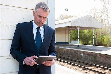 Businessman using digital tablet on railway platform Stock Photo - Premium Royalty-Free, Code: 649-08125971