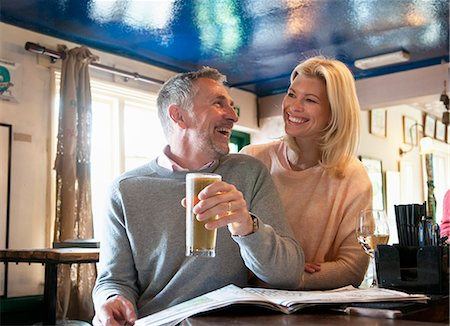 Couple laughing and reading newspaper in pub Stock Photo - Premium Royalty-Free, Code: 649-08125973