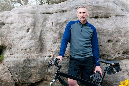 Portrait of male mountain biker on rock formation Stock Photo - Premium Royalty-Free, Code: 649-08125989