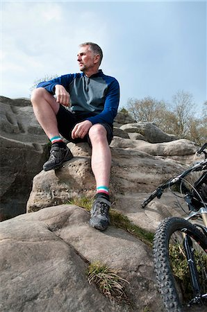 Mature male mountain sitting and looking out from rock formation Stock Photo - Premium Royalty-Free, Code: 649-08125991