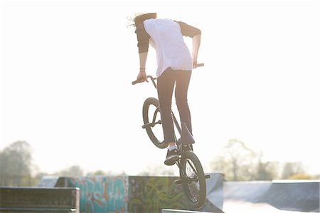 Young man doing stunt on bmx at skatepark, rear view Stock Photo - Premium Royalty-Free, Code: 649-08144671