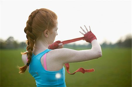 Portrait of a woman putting on boxing gloves straps in the park Stock Photo - Premium Royalty-Free, Code: 649-08144702