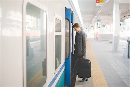 Young businessman commuter boarding train with suitcase. Stock Photo - Premium Royalty-Free, Code: 649-08144791