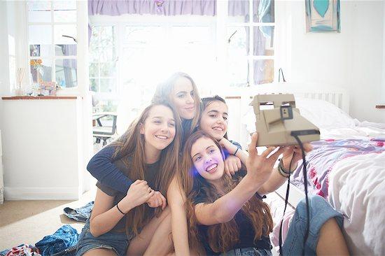 Four teenage girls taking instant camera selfie in bedroom Stock Photo - Premium Royalty-Free, Image code: 649-08145141