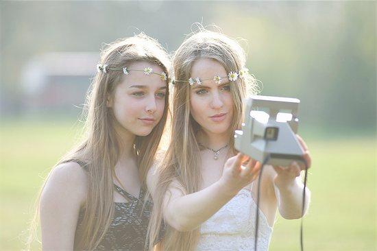 Two teenage girls in park  taking instant camera selfie Stock Photo - Premium Royalty-Free, Image code: 649-08145179