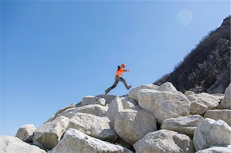 piles of work - Worker jumping on stack of boulders at quarry Stock Photo - Premium Royalty-Free, Code: 649-08145199