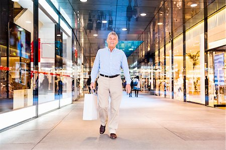 shopping mall - Senior man walking through shopping mall holding bag Stock Photo - Premium Royalty-Free, Code: 649-08145232