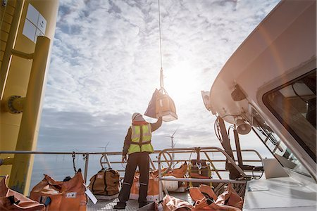 supervising - Deck worker winching parts up to wind turbine on offshore windfarm Stock Photo - Premium Royalty-Free, Code: 649-08145368