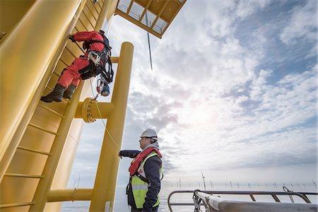 supervising - Engineer climbing wind turbine at offshore windfarm Stock Photo - Premium Royalty-Free, Code: 649-08145372
