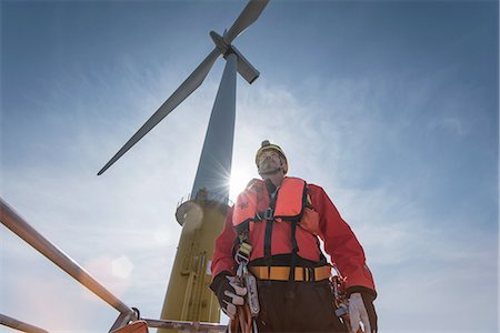 Engineer preparing to climb windturbine at offshore windfarm, low angle view Stock Photo - Premium Royalty-Free, Code: 649-08145387