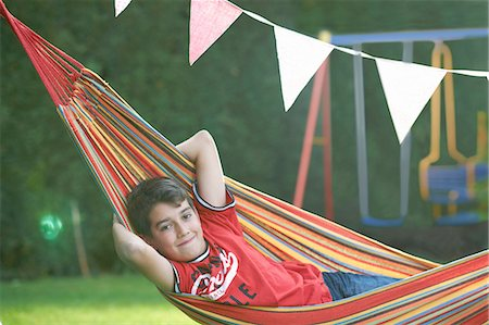 Portrait of confident boy reclining in striped garden hammock with hands behind head Stock Photo - Premium Royalty-Free, Code: 649-08145729