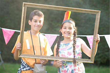 preteen girl pigtails - Boy and girl looking through picture frame, smiling, looking at camera Stock Photo - Premium Royalty-Free, Code: 649-08179761