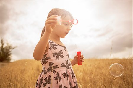 pink - Girl blowing bubbles in wheat field Stock Photo - Premium Royalty-Free, Code: 649-08179891