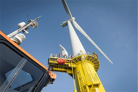 Engineers climbing wind turbine from boat at offshore windfarm, low angle view Stock Photo - Premium Royalty-Free, Code: 649-08179964