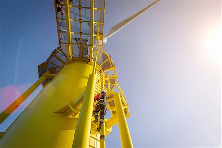 Engineers climbing wind turbine from boat at offshore windfarm, low angle view Stock Photo - Premium Royalty-Free, Code: 649-08179965