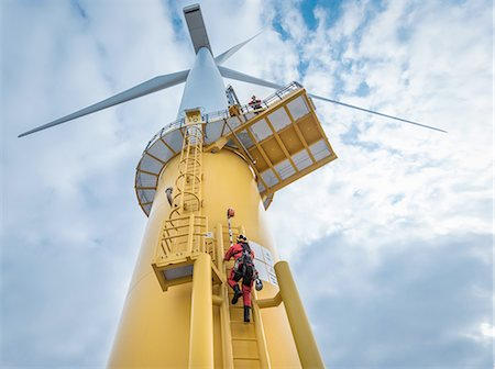 energia - Engineers climbing wind turbine from boat at offshore windfarm, low angle view Fotografie stock - Premium Royalty-Free, Codice: 649-08179969