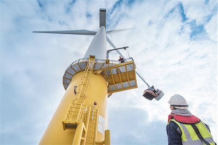 Engineers winch tools up wind turbine from boat at offshore windfarm, low angle view Stock Photo - Premium Royalty-Free, Code: 649-08179970