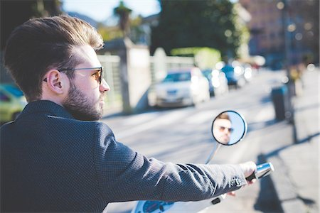 dark glasses - Stylish young man looking away from moped Stock Photo - Premium Royalty-Free, Code: 649-08180063