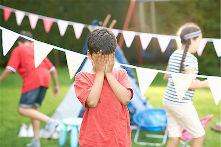 Boy covering his eyes for hide and seek with brother and sister in garden Stock Photo - Premium Royalty-Free, Code: 649-08180244