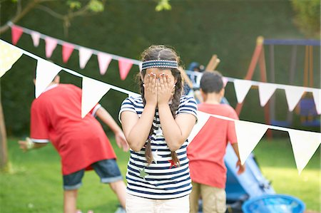 Girl covering her eyes for hide and seek with brothers in garden Stock Photo - Premium Royalty-Free, Code: 649-08180245
