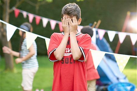Boy covering his eyes for hide and seek with sister and brother in garden Stock Photo - Premium Royalty-Free, Code: 649-08180246