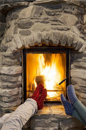 Cropped shot of two young women with feet up in front of fireplace Stock Photo - Premium Royalty-Free, Code: 649-08180249