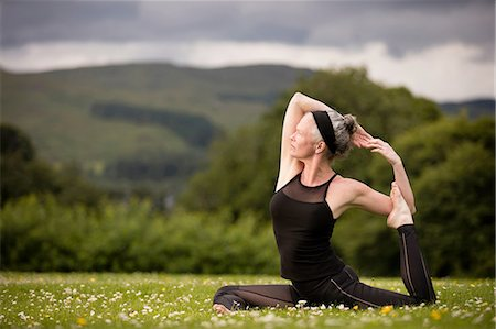 Mature woman doing splits practicing yoga in field Stock Photo - Premium Royalty-Free, Code: 649-08180520