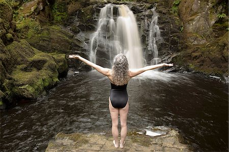 Rear view of mature woman practicing with open arms in front of waterfall Stock Photo - Premium Royalty-Free, Code: 649-08180546