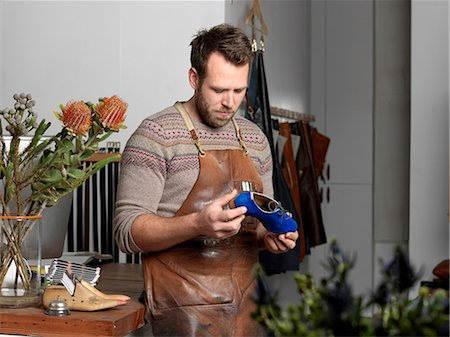 Shoemaker holding blue shoe in workshop Stock Photo - Premium Royalty-Free, Code: 649-08237572