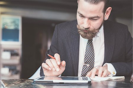 style - Businessman making diary notes from digital tablet at cafe table Stock Photo - Premium Royalty-Free, Code: 649-08237671
