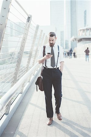 Businessman reading smartphone text update whilst walking on footbridge Stock Photo - Premium Royalty-Free, Code: 649-08237681