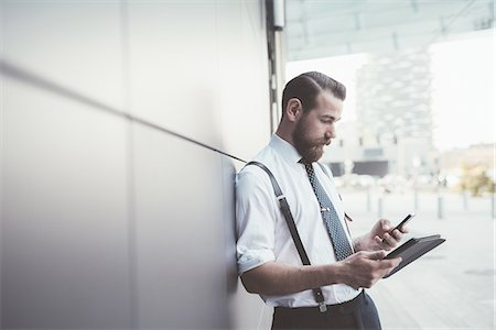 style - Stylish businessman using smartphone and digital tablet outside office Stock Photo - Premium Royalty-Free, Code: 649-08237695