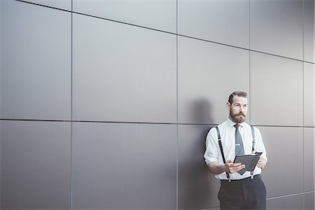 Stylish businessman using digital tablet and smartphone leaning against office wall Stock Photo - Premium Royalty-Free, Code: 649-08237696