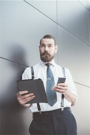 Stylish businessman using smartphone and digital tablet leaning against office wall Stock Photo - Premium Royalty-Free, Code: 649-08237698