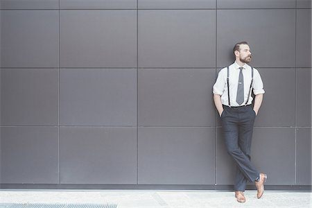 Stylish businessman with hands in pockets leaning against office wall Stock Photo - Premium Royalty-Free, Code: 649-08237693