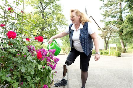Mid adult woman with prosthetic leg, in garden, watering plants Stock Photo - Premium Royalty-Free, Code: 649-08237706