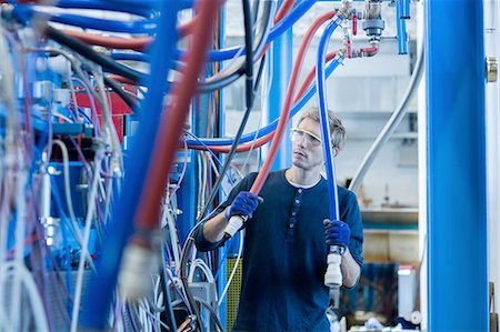 Factory technician inspecting network cables Stock Photo - Premium Royalty-Free, Code: 649-08237742