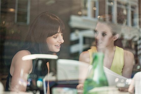 Two young brunette women sitting in a cafe talking having a business meeting Stock Photo - Premium Royalty-Free, Code: 649-08237857