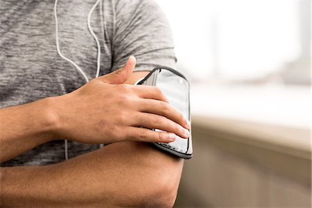 finger - Cropped shot of male runner choosing music on smartphone armband Stock Photo - Premium Royalty-Free, Code: 649-08238082