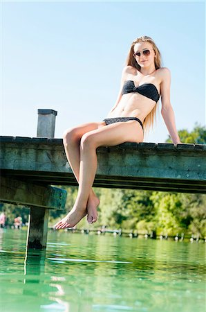 dangling - Low angle view of young woman wearing bikini and sunglasses hanging legs off pier Stock Photo - Premium Royalty-Free, Code: 649-08238137