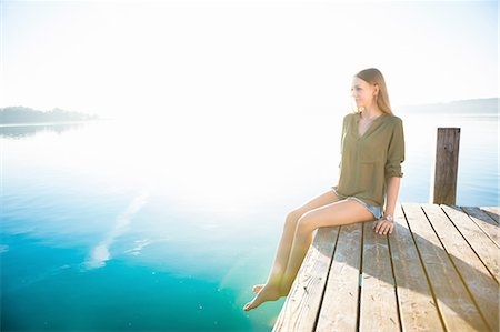 dangling - Young woman sitting hanging legs off wooden pier looking away Stock Photo - Premium Royalty-Free, Code: 649-08238138