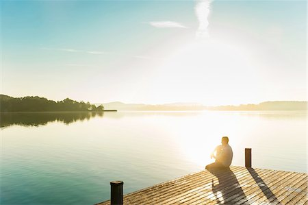Young man sitting on corner of pier of sunlit lake, Woerthsee, Bavaria, Germany Stock Photo - Premium Royalty-Free, Code: 649-08238159